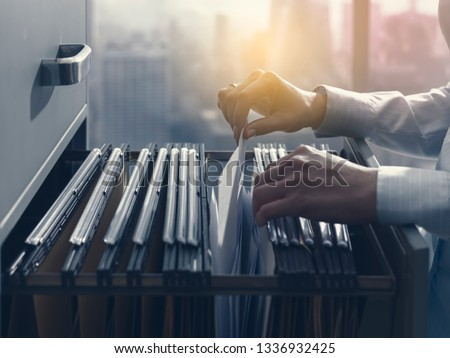 Professional female office clerk searching files and paperwork in the filing cabinet