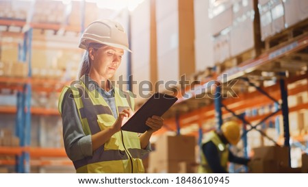 Professional Female Worker Wearing Hard Hat Checks Stock and Inventory with Digital Tablet Computer in the Retail Warehouse full of Shelves with Goods. Working in Logistics, Distribution Center