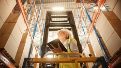 Professional Female Worker Wearing Hard Hat Lifts Herself on Aerial Work Platform to Check Stock and Inventory with Digital Tablet on the Higher Level of Retail Warehouse full of Shelves with Goods