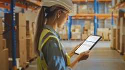 Professional Female Worker Wearing Hard Hat Uses Digital Tablet Computer with Inventory Checking Software in the Retail Warehouse full of Shelves with Goods. Delivery, Distribution Center.