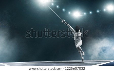 Professional fencer girl in fencing mask with rapier