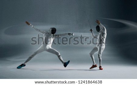 Professional fencers in fencing mask with rapier