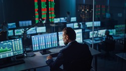 Professional Financial Data Analysts Working in a Modern Monitoring Office with Live Analytics Feed on a Big Digital Screen. Monitoring Room with Finance Specialists Sit in Front of Computers.