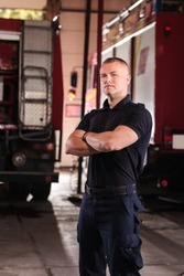 Professional fireman portrait. Firefighter wearing uniform of shirt and trousers. Fire truck in the background.