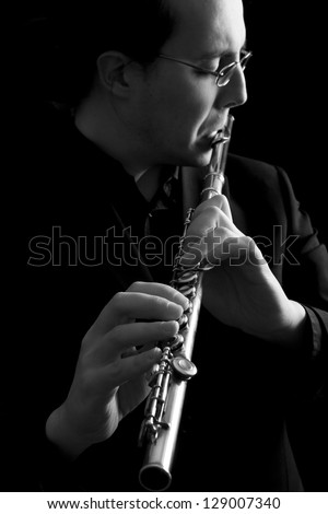 professional flutist musician playing flute on black background