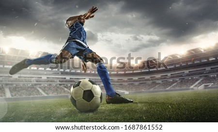 Professional football or soccer player in action on stadium with flashlights, kicking ball for winning goal, wide angle. Concept of sport, competition, motion, overcoming. Field presence effect.