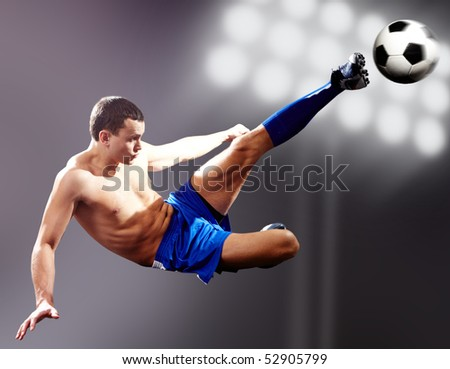 Professional footballer kicking soccer ball