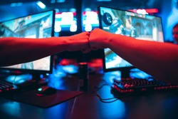 Professional gamer greeting and support team fists hands online game in neon color blur background. Soft focus, back view.