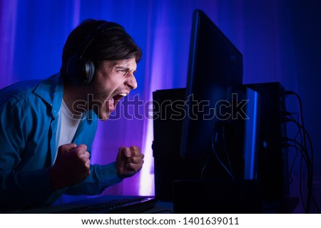 Professional Gamer Playing and Winning in Shooter Online Video Game. Room Lit by Neon Lights