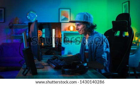 Professional Gamer Playing First-Person Shooter Online Video Game on His Powerful Personal Computer with Colorful Neon Led Lights. Young Man is Wearing a Cap. Living Room Lit with Green Lamps. Evening