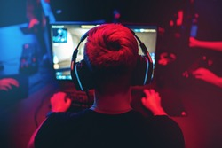 Professional gamer playing online games tournaments pc computer with headphones, Blurred red and blue background.