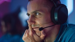 Professional Gamer Plays Computer Video Game on a Championship, Thinking About Strategy and Tactics. Team of Pro Gamers Play in Computer Game. Stylish Neon Cyber Games Arena. Closeup Portrait View