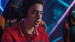 Professional Gamer Plays Computer Video Game Talking into Headset with Teammates on Championship. Diverse Esport Team of Pro Gamers Play in Computer Game. Stylish Neon Cyber Games Arena. Portrait Shot