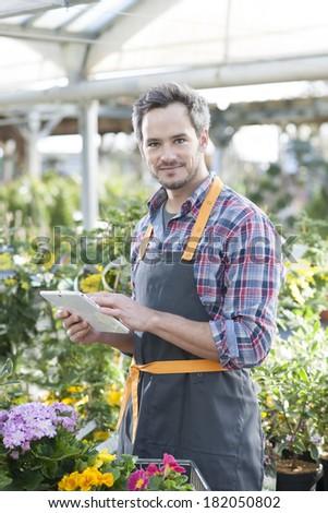 Professional gardener using a digital tablet in a garden center