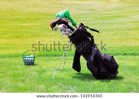 Professional golf equipment  in a golf cart and bucketful of balls on the golf course