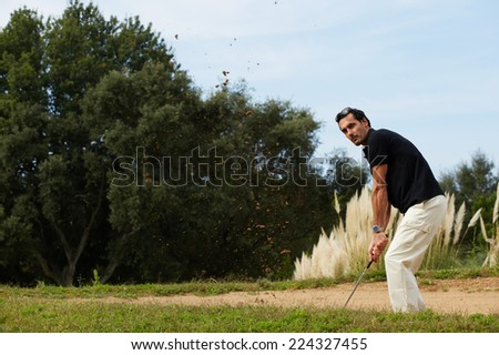 Professional golf player in action hitting golf ball, strong golf shot of handsome adult player standing on beautiful golf course