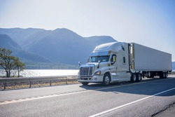 Professional grade big rig semi truck with chrome accessories transporting frozen cargo in refrigerated semi trailer moving on the road along river with bewitching view on the opposite bank