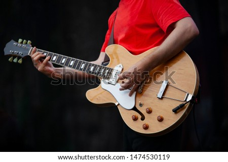 Professional guitarist man playing live set on stage with electroacoustic guitar in hand.Guitar player performing solo part on scene during summer music festival outdoor.Classic rocker plays song