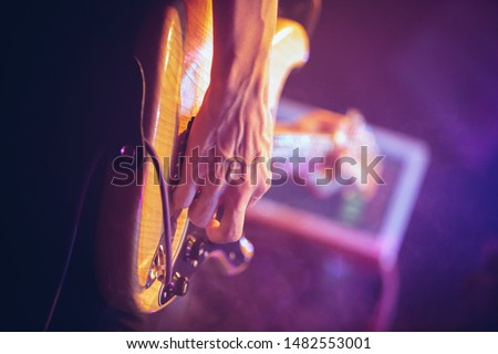 Professional guitarist plays solo part on electric bass guitar in nightclub.Rock musician playing on string instrument in music hall.Focus on musicians hands and strings.Pro audio equipment on stage