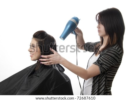 Professional hair stylist blowing out client's hair