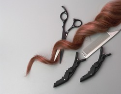 Professional Hairdresser Equipment on Gray Background. Scissors, Comb, Hairclip and Strand of Curly Hair, Flat Lay