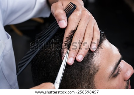 Professional hairdresser is cutting men\'s hair in beauty salon.