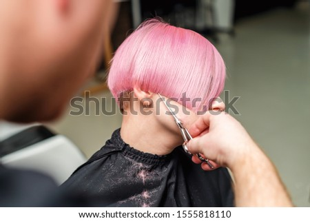 Professional hairdresser is cutting short pink hair of young woman in beauty salon.