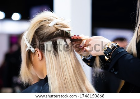 Professional hairdresser making hair extensions for blonde girl in a beauty salon Stockfoto ©