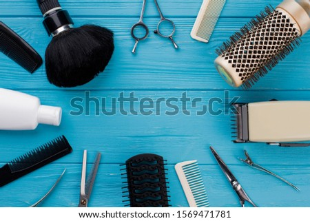 Professional hairdresser tools on blue background. Hairdressing equipment and copy space.