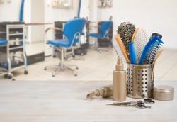 Professional hairdresser tools on table over defocused salon interior background.