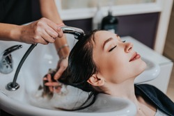 Professional hairdresser washing hair of a beautiful young  woman in hair salon.
