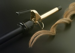 Professional Hairdressing Curling Iron With A lock Of Wavy Hair On Black Background, Spotted With Ray Of Green Lights