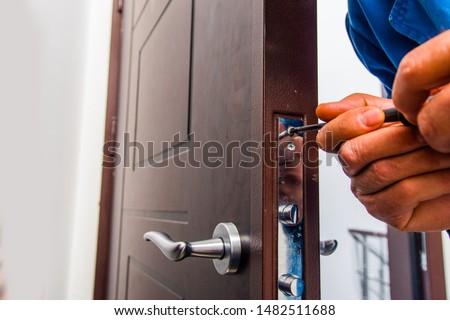 Professional handyman is fixing the door lock