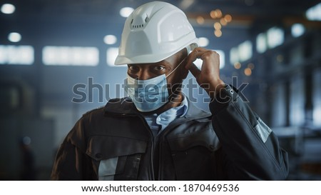 Professional Heavy Industry Engineer Worker is Putting On Safety Face Mask in a Steel Factory. Black African American Industrial Specialist in Hard Hat Standing in a Metal Construction Manufacture. Foto stock ©