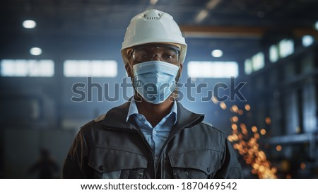 Professional Heavy Industry Engineer Worker Wearing Safety Face Mask, Uniform, Glasses and Hard Hat in a Steel Factory. African American Industrial Specialist Standing in Metal Construction Facility.