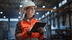 Professional Heavy Industry Engineer Worker Wearing Safety Uniform and Hard Hat Uses Tablet Computer. Serious Successful Female Industrial Specialist Walking in a Metal Manufacture Warehouse.