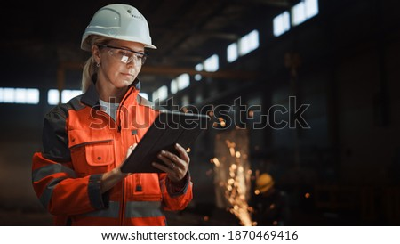 Professional Heavy Industry Engineer Worker Wearing Safety Uniform and Hard Hat Uses Tablet Computer. Serious Successful Female Industrial Specialist Standing in a Metal Manufacture Warehouse.