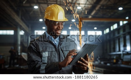 Professional Heavy Industry Engineer Worker Wearing Safety Uniform and Hard Hat Uses Tablet Computer. Smiling African American Industrial Specialist Standing in a Metal Construction Manufacture.