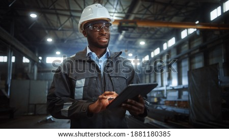 Professional Heavy Industry Engineer Worker Wearing Safety Uniform and Hard Hat Uses Tablet Computer. Smiling African American Industrial Specialist Walking in a Metal Construction Manufacture.