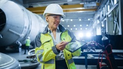 Professional Heavy Industry Female Engineer Wearing Safety Uniform, Holds Digital Tablet Computer and Explains Product Design. Industrial Factory Construction of Oil, Gas and Fuels Transport Pipeline