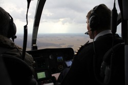 professional helicopter pilot, military might. Outside the window, or the board is clear of the field, steppe, clouds and sun rays. Helicopter without rear propeller McDonnell Douglas, Notaro