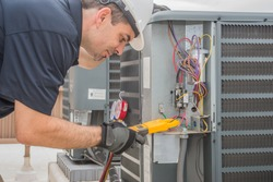 Professional hvac technician measuring amperage on an air conditioner unit