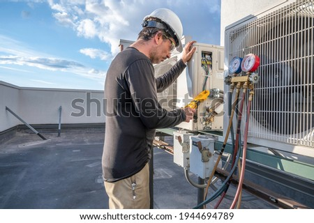Professional HVAC technician taking an amperage reading on a mini-split ductless air conditioning system.