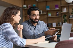 Professional indian teacher, executive or mentor helping latin student, new employee, teaching intern, explaining online job using laptop computer, talking, having teamwork discussion in office.
