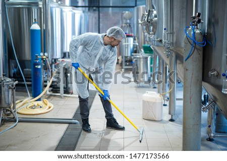 Professional industrial cleaner in protective uniform cleaning floor of food processing plant. Cleaning services.