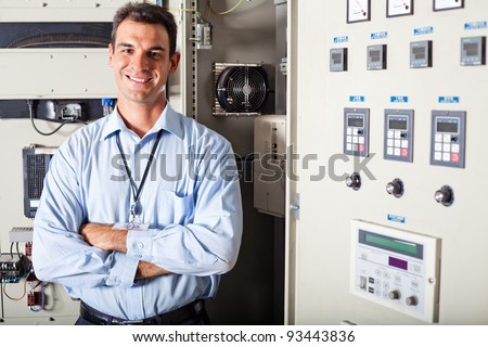 professional industrial technician in front of computerized machinery