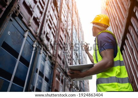 Professional industry worker of logistic concept.Engineer or foreman control loading Containers box from Cargo freight ship for import export,Engineer worker checking quantity of product in containers Zdjęcia stock ©