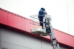 Professional installation work on a construction building site. Assemblers perform high-altitude installation works on the lifts platforms.
