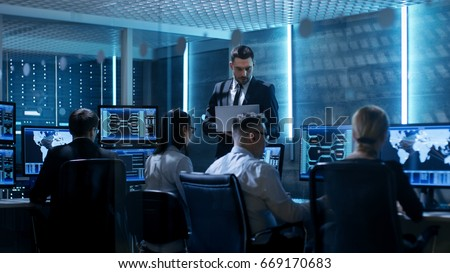 Professional IT Engineers Working in System Control Center Full of Monitors and Servers. Supervisor Holds Laptop and Holds a Briefing. Possibly Government Agency Conducts Investigation.