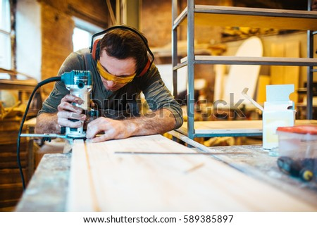 Professional joiner with wood-router cutting wooden plank